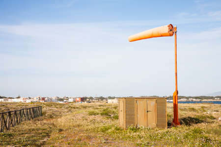 An orange windsock standing on the heliport of Favignana with a strong wind blowing Stock Photo