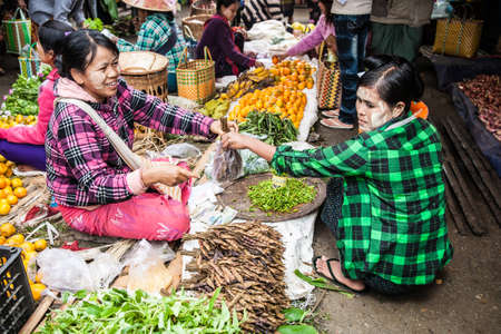 Nyaungshwe, Myanmar - 2017, January 4 : A female hawker or vendor selling tamarind to a female customer, both wearing thanaka cream, in a street market in the town of Nyaungshwe on the Inle Lake of central Burma