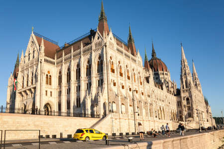 Budapest, Hungary - 2017, May 28 : The parliament building of Budapest at sunset as seen from the river bank of the Danube river with people