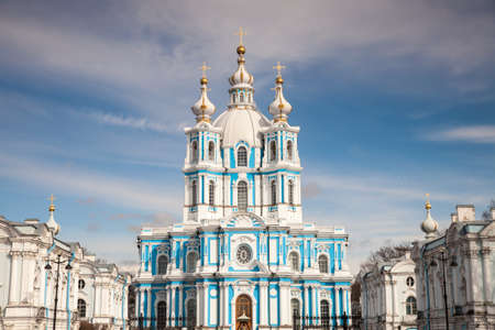 The facade of the blue and white Orthodox Smolny Cathedral in the Russian town of Saint Petersburg against a blue sky with some clouds, Russia 版權商用圖片