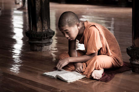 Nyaung Shwe, Myanmar - 2017, January 4 : A young novice buddhist monk studying in a book in the Shwe Yan Pyay monastery in Nyaung Shwe near the Inle Lake