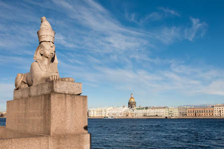 An ancient 3500 year old Egyptian sphinx positioned on the University Embankment next to the Neva river with a view on the city's quayside, Saint Petersburg, Russia Reklamní fotografie