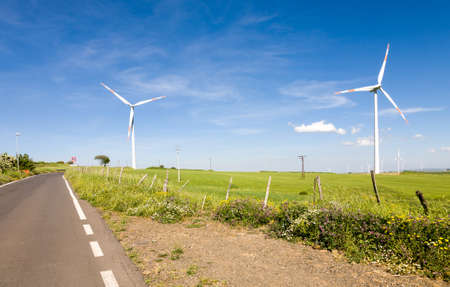 A number of turbines in a green field next to a road generating clean energy using wind as a renewable energy source in Sicily, Italy