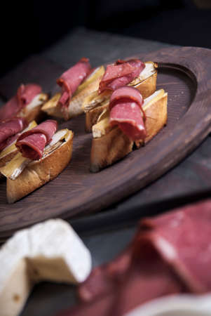 Bread Brie Cheese and Rolled Pastrami with Nuts and Honey on a Wooden Tray Stock Photo