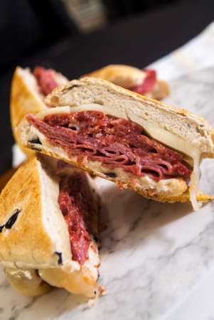 Classic Reuben Sandwich with Provolone Cheese on a White Veined Marble Background
