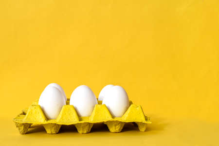 White Eggs in a Viol on Yellow Background