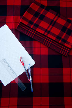 Paper, Ruler and Pens on a Red and Black Gingham Fabric Stock fotó