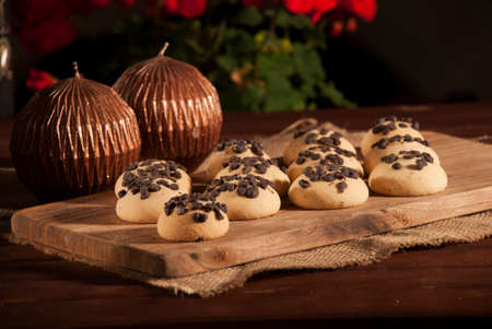 Cookies with Drop Chocolate on a Wooden Board with Red Flowers