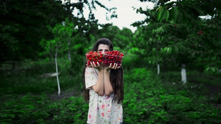 keep your hands: The girl holds two boxes filled with strawberries and cherries against the backdrop of the garden. Conception: choice food vegan