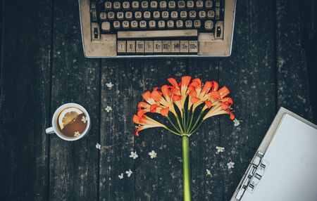 typewriting: A cup of tea and an old typewriter, around her are flowers and a cup of tea on.