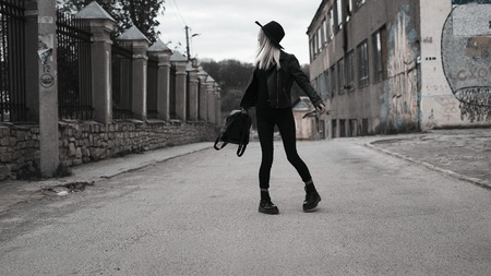 A stylish girl in a hat with white hair, dressed in black clothes, walks around the city and twists her bag. Stock Photo