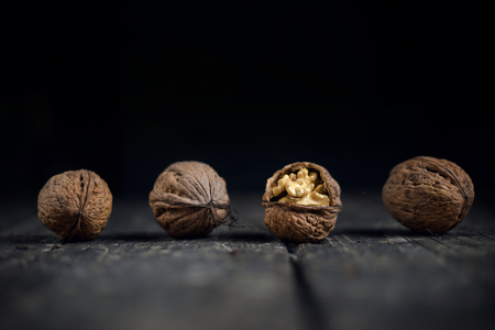 Walnuts on a grey textured wooden table. Assortment of nuts isolated on rustic old wooden background and splintered walnut with heart-shaped core. Walnuts close up. Stock Photo