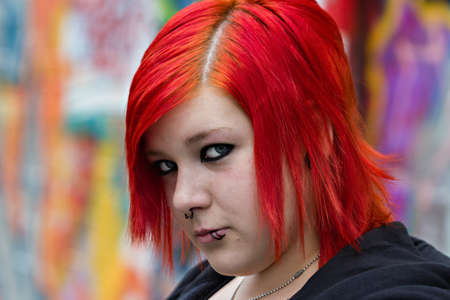 graffito: Cheeky red-haired girl with piercing in front of graffito wall