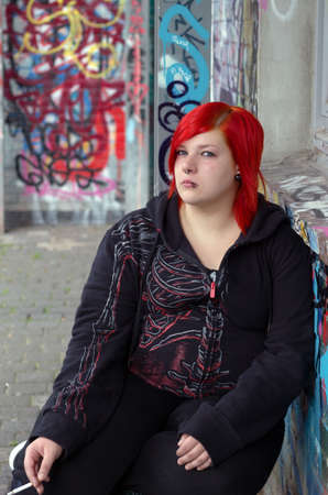 Smoking red-heared girl on graffito background photo