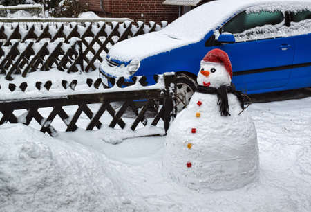 Snowman in front of a house in the city  photo