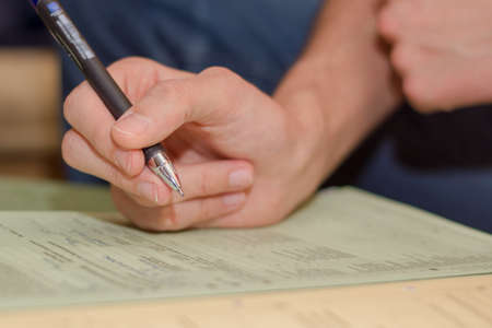 Young man fills out a form photo