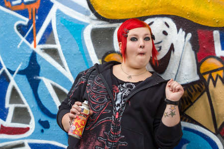 graffito: Redhead woman with piercing and funny face with graffity spray