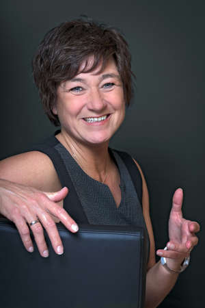 told: Mature funny woman sitting on the chair in front of black background and told