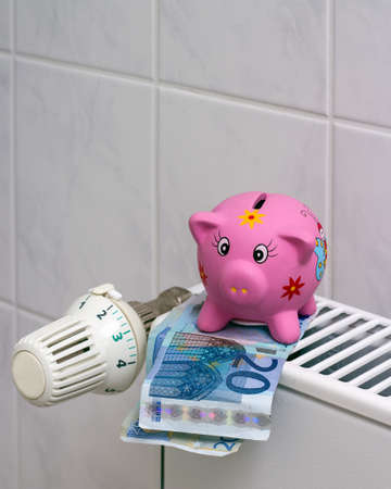 Save energy   Piggy bank with euro banknotes next to a thermostat on the heating photo