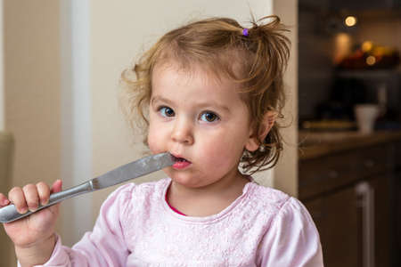 Baby girl is left unattended and holds a knife in his mouth Stock Photo