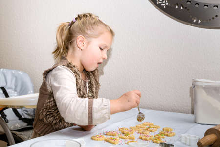 suger: Little girl decorating cookies with suger sprinkles Stock Photo