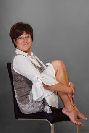 Full body portrait of a funny woman, sitting barefoot on a chair photo