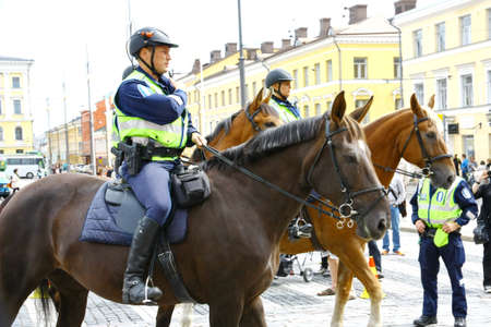 HELSINKI, FINLAND - JUNE 30: Mounted police protect people taking part in the annual Helsinki Pride gay parade in Helsinki, Finland on June 30, 2012.  Stock Photo - 17436040