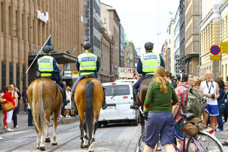 HELSINKI, FINLAND - JUNE 30: Mounted police protect people taking part in the annual Helsinki Pride gay parade in Helsinki, Finland on June 30, 2012.  Stock Photo - 17436362