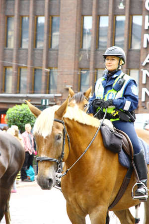 HELSINKI, FINLAND - JUNE 30: Mounted police protect people taking part in the annual Helsinki Pride gay parade in Helsinki, Finland on June 30, 2012.