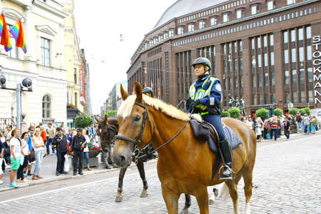 HELSINKI, FINLAND - JUNE 30: Mounted police protect people taking part in the annual Helsinki Pride gay parade in Helsinki, Finland on June 30, 2012.  Stock Photo - 17437169
