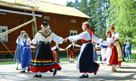 HELSINKI, FINLAND - JUNE 20, 2012: Unidentified dancers in folklore ensemble in traditional folk costumes at midsummer day festival. For editorial use only.