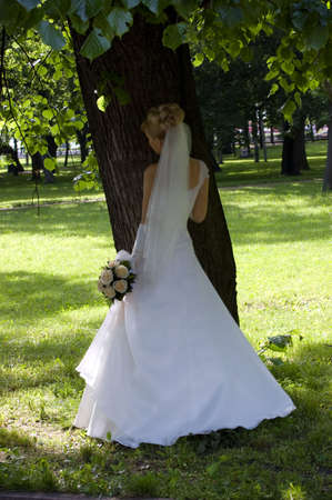 Bride under tree, white dress, foliage photo