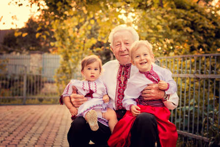 A portrait of a grandfather and grandchildren at the yard photo