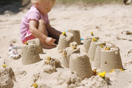 Little girl making sand castles Stock Photo