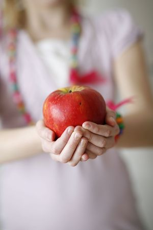 Girls hands holding a red apple