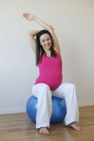 A young smiling pregnant woman in a pink shirt doing an upper body stretching exercise while sitting on blue fitness ball.