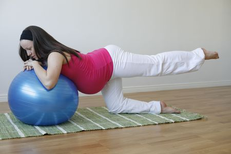 A young pregnant woman in a pink shirt doing a buttock and leg muscle exercise using a blue fitness ball.