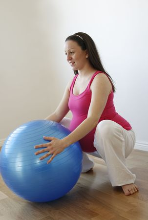 A young smiling pregnant woman in a pink shirt doing a squatting exercise with a blue fitness ball while standing up. Stock Photo