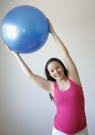 A young smiling pregnant woman in a pink shirt exercising and stretching using a blue fitness ball while standing up.