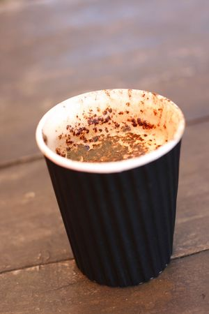 A delicious cappuccino in a take-away cup on a wooden table..