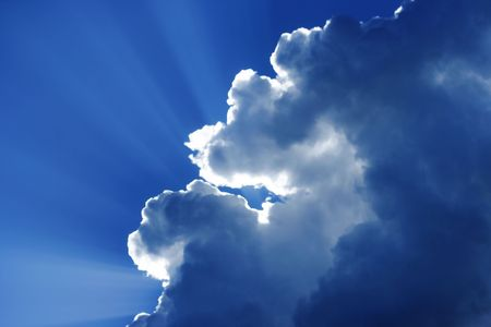 Sun shining behind the clouds on a brilliant blue sky with beautiful illumination effects. Фото со стока