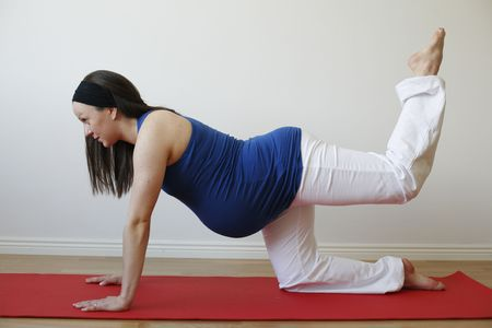 A young pregnant woman doing a buttock and leg muscle exercise on a mat.