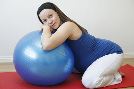 A young pregnant woman doing a relaxation exercise using a fitness ball on an exercise mat. Stock Photo
