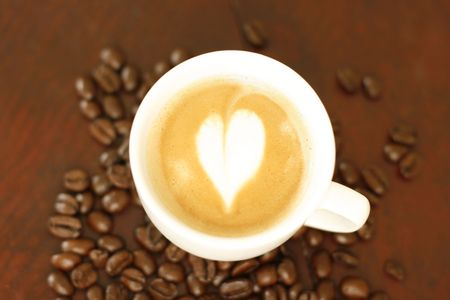 Top down view of a delicious piccolo latte with a heart shaped coffee art design. photo