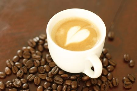 A delicious piccolo latte in a small white cup with a heart shaped coffee art design. photo