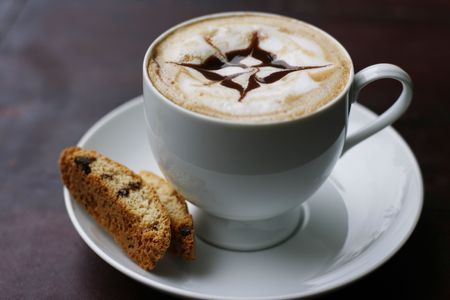 A delicious cappuccino with a professional coffee art chocolate sauce star design in a cup on a saucer with a decorative biscotti biscuit.