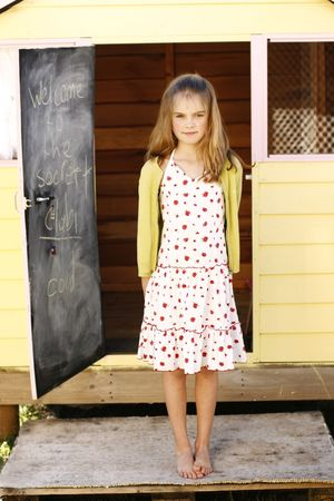 A portrait of pretty and happy young girl standing at the front of her playhouse. photo