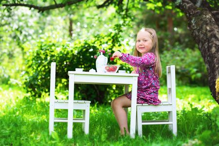A smiling little girl sitting at a white table having a tea party in a garden setting on a sunny summer day while holding a delicious strawberry.