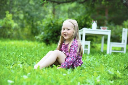 A portrait of a smiling happy little girl sitting on the grass in a garden with a white table and chairs in the background. photo