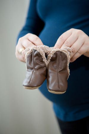 Pregnant mother holding cute little leather baby booties in front of her round tummy photo